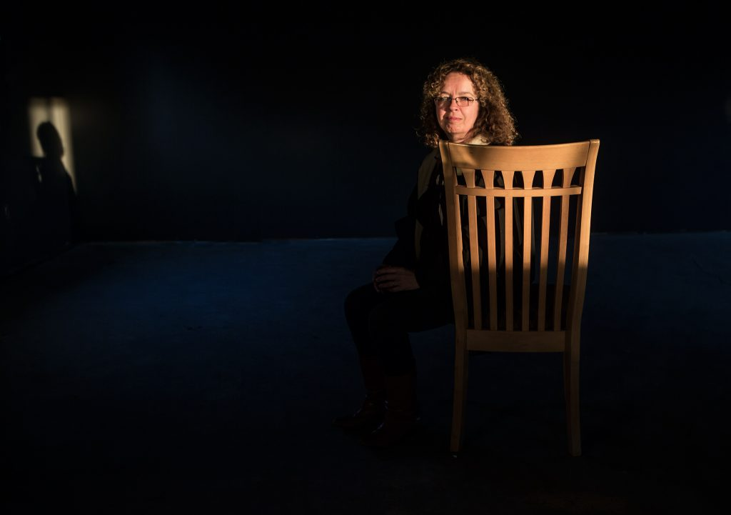 A woman in a chair in a darkened room. There is one light on her that casts her shadow on a far wall.