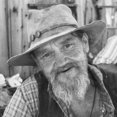I photographed this man in Oatman, CA as I was driving along RT 66. He was seated at a table near a deserted gold mine, and looked like an old prospector. He was holding a six-shooter when I walked up.