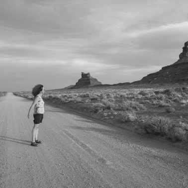 A woman standing in the middle of a dirt road in Valley of the Gods, Utah. She is photographed from the side in black and white. She seems in awe of the rock monuments.