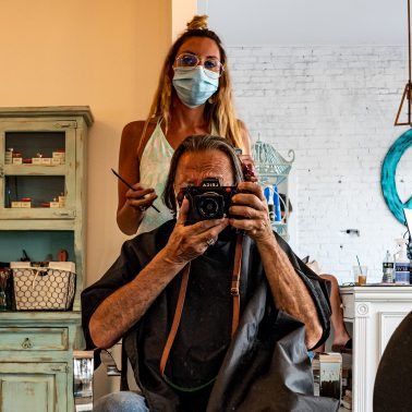 A self-portrait shot into the mirror while getting a haircut. The hair stylist is wearing a pandemic mask..