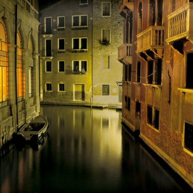 A photograph of a Venice Canal at night lit by the running lights of a water taxi.