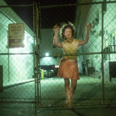 A woman in Miami, late at night looking through a page fence. Her hands are on the fence at face height.