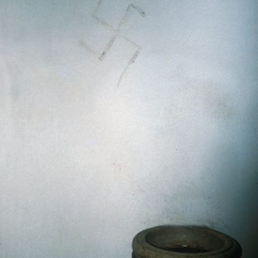 Swastika scratched over holy water photographed in a church in Salzburg, Austria - circa 1989