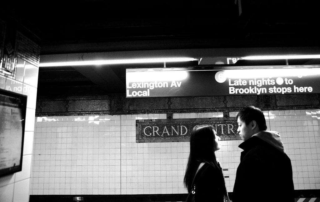 A young couple looking into each other's eyes while waiting for a subway train at Grand Central Station, NYC