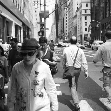 A black and white photo of people walking south on 5th avenue on a warm autumn afternoon. circa 2019.