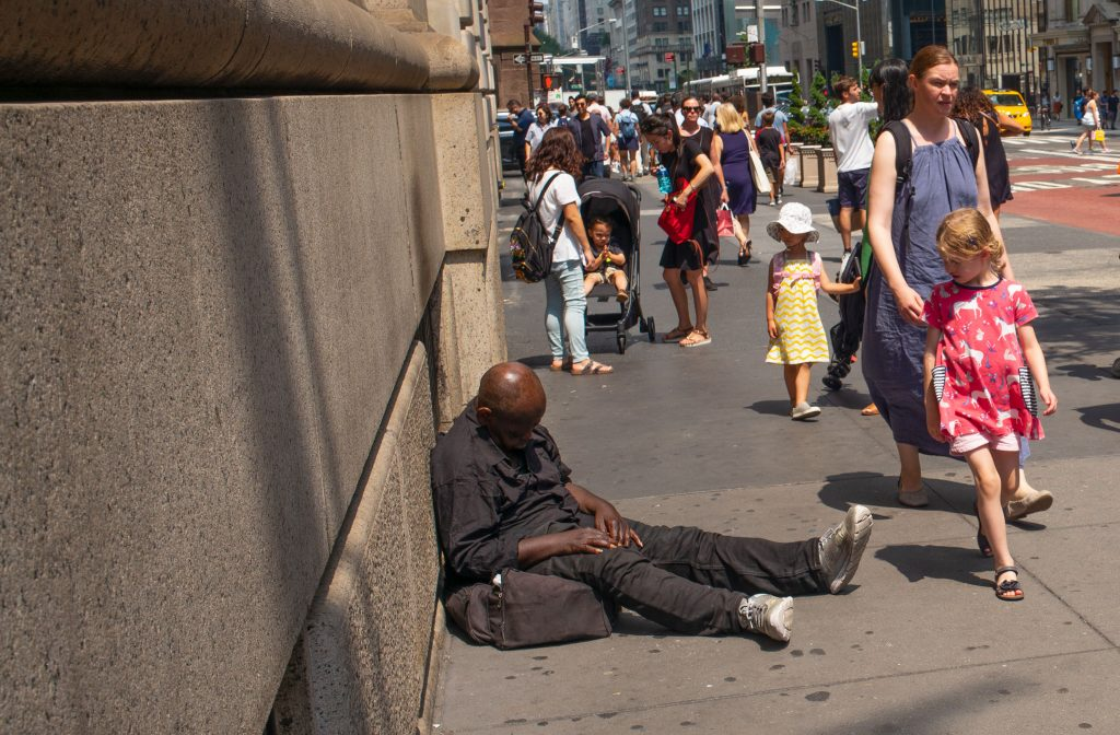 A man is sleeping on a 5th Avenue sidewalk and as people pass, only the children seem to see him.