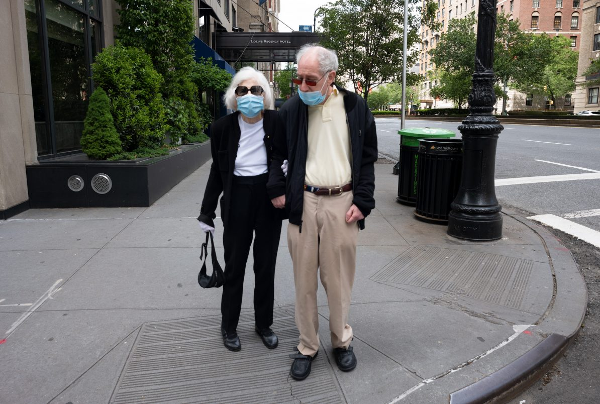 an elderly couple, wearing medical masks. They are out for a walk on 5th avenue during the pandemic of 2020.
