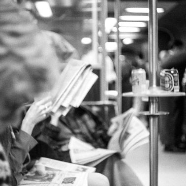 Black and white photo of people reading as they sit in the bar car on Metro North circa 1990