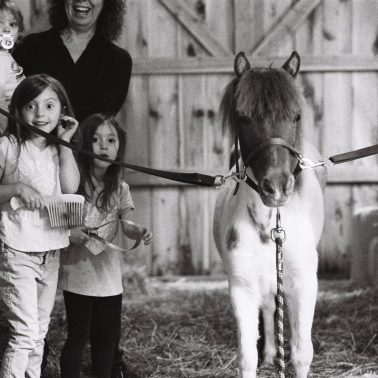 A woman is holding a child and with her are two other femal children and a pony named Zila