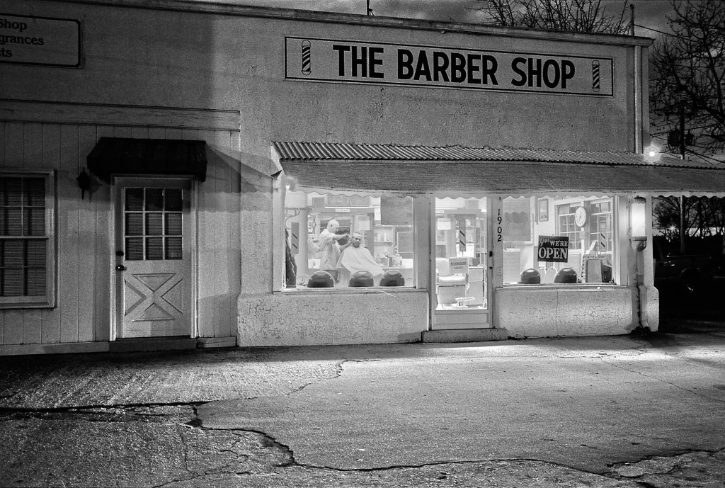 A night time black and white photo from the outside looking in at a barber shop.