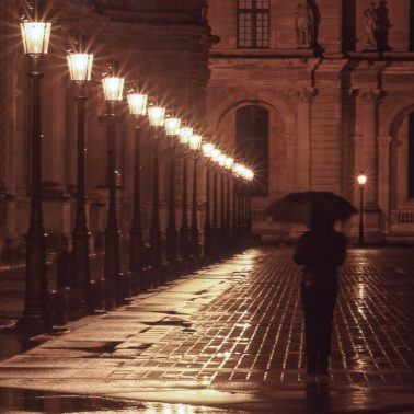 A woman with an umbrella, walking near the Louvre in Paris at 3 AM. Streetlights reflect in the wet cobble walkway.