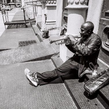 A black and white photo of a man in NYC, sitting on a step, playing the trumpet.