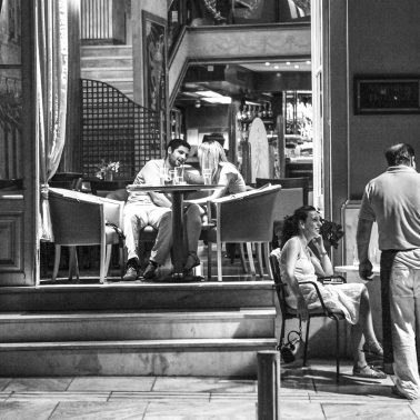 A black and white photograph of people dining outside at night at a restaurant in Athens, Greece,