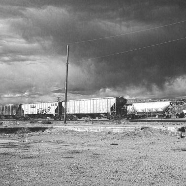 Black and white photograph of a train and some silos in Gallup, New Mexico.