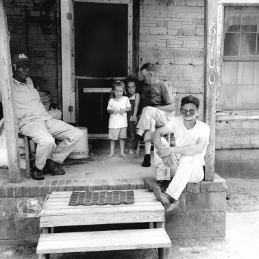 Three men and two little girls on a wooden porch in North Carolina.