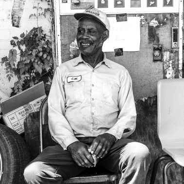 A man sitting in an old folding chair, by a broken soda machine, behind an appliance store in Arkansas