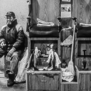 A black and white photograph of a man who sines shoes at Grand Central Station