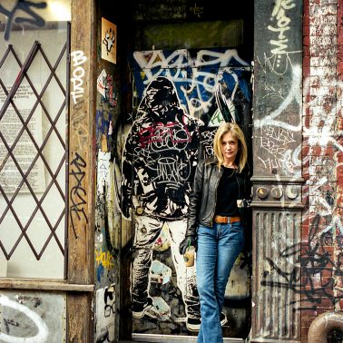 A young attractive woman standing in a doorway that has been covered in graffti.