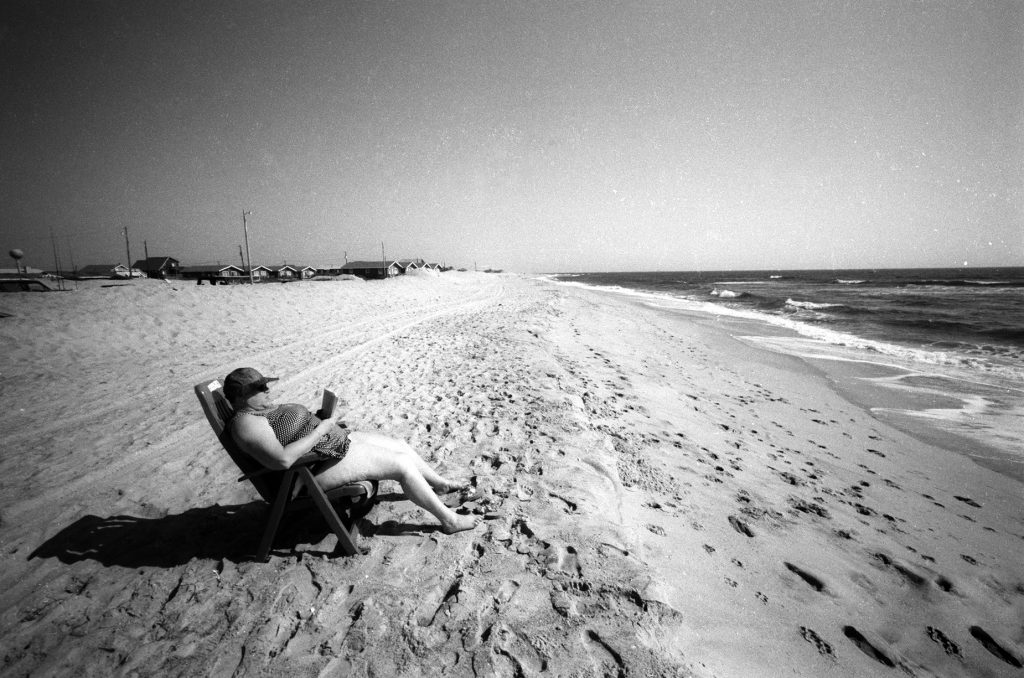A single person in a bathing suit and a hat, seated in a beach chair, reading a book.