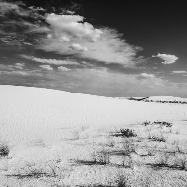 A black and white photograph taken by Frank Blackwell of a sand dune under a partially cloudy sky in White Sands National Park, New Mexico