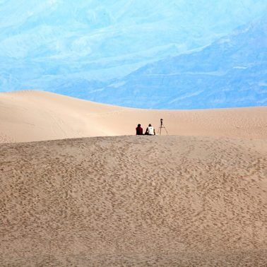 Two photographers sitting on a distant sanddune waiting for the light to change.