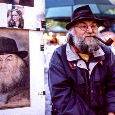 An artist in Paris, seated by a self-portrait he paited of himself.