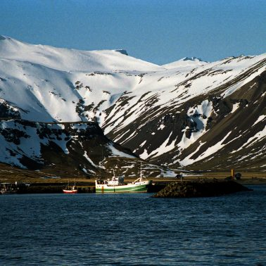 A color photograph of an Icelandic fishing boat docked under a snow capped mountain.
